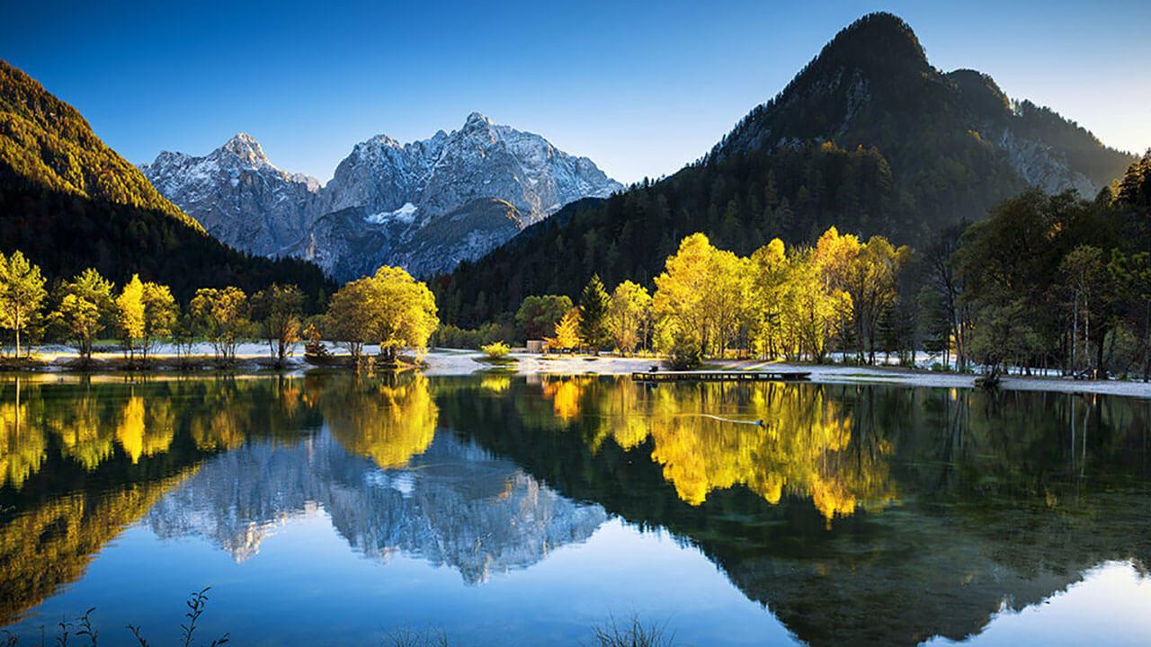 عکس کوه و درختان درباره نشان دادن عظمت منظره با استفاده از بازتاب مربوط به ۵ اصل کلیدی برای بهبود ترکیب بندی در عکاسی منظره